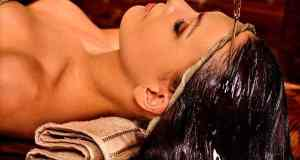 Woman having Shirodhara pouring oil on head in India spa .