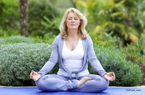 mature woman doing lotus yoga positio outside in the garden