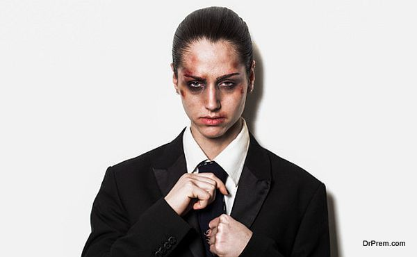 Beaten up girl wearing coat and tie and looking
