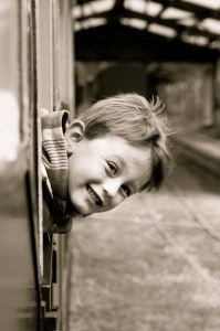 Little boy leaning out of a train window