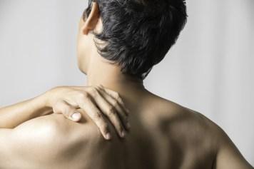 Man holding shoulder due to shoulder pain