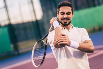man playing tennis with hurt elbow