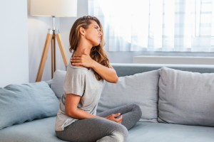 woman sitting on the bed and holding painful shoulder with another hand.