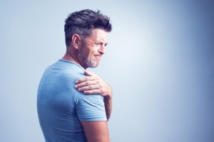middle aged man experiencing shoulder pain on grey background