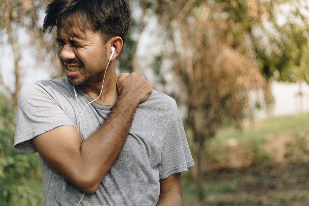 young asian man have shoulder pain after running and exercising