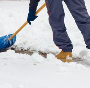 Close-up as man shovels snow