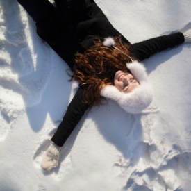 Happy girl lying in the deep snow on beautiful winter day.