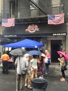 Anna lining up in the rain for a hotdog at a biker bar.