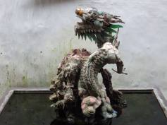 A dragon made of bits of old ceramic bowls and cups