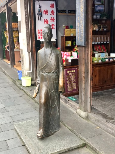A statue out the front of a traditional Chinese medicine store