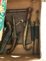 Some old pistols and daggers for sale in a box in the nice flea market