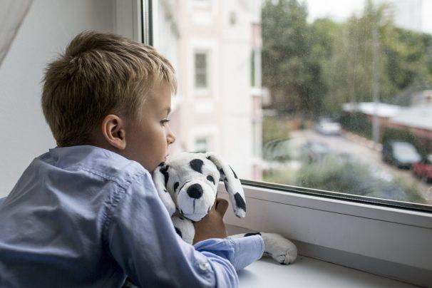 little boy with a toy near a window