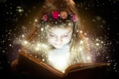 Beautiful little girl reading magic book