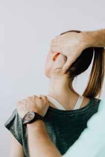 crop anonymous orthopedist examining neck of faceless lady in hospital