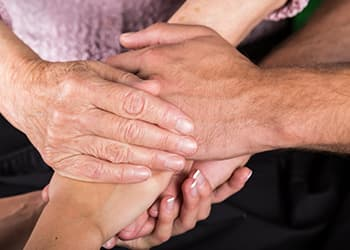 support group with hands in center of circle