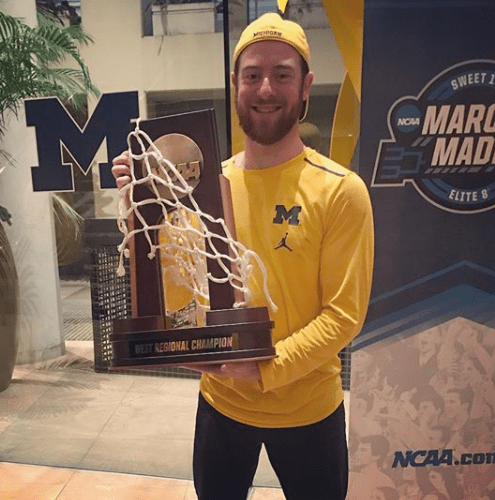 Aaron Ginns with University of Michigan's NCAA basketball final four trophy