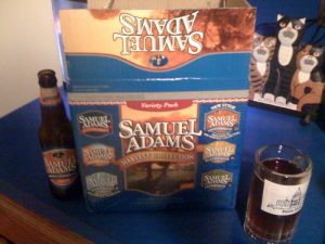 Samuel Adams Harvest 12-pack with an open bottle of Harvest Pumpkin Ale
