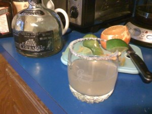 A rocks glass with salt on rim and a lime wedge. The glass contains a Margarita made with Cointreau and La Cofradia Añejo tequila