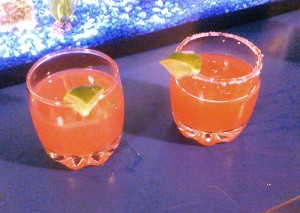 Two glasses with Cranberry Margaritas and lime wedges. The glass on the right has a salted rim.