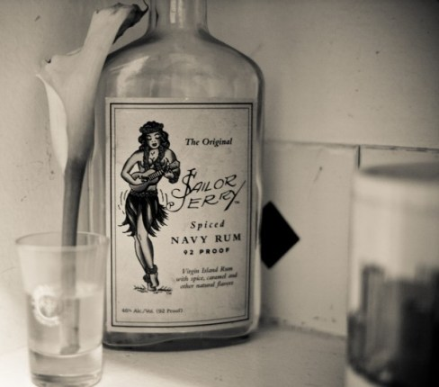 A black and white photo of Sailor Jerry Spiced Navy Rum with a lily in a glass in the foreground