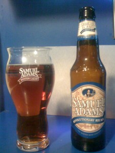 Samuel Adams Revolutionary Rye Ale poured into a glass, next to the bottle.