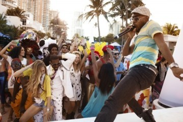 A diverse group of young people dancing on an outdoor pavilion in Barbados
