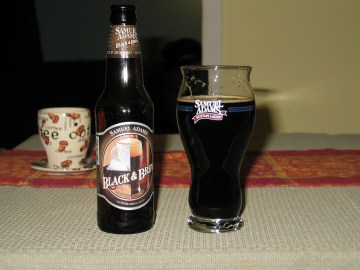 A bottle of Sam Adams Black and Brew beer next to a Samuel Adams specialty beer glass filled with the dark Black and Brew stout.