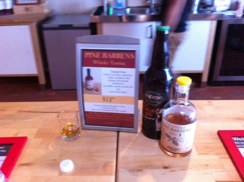 A shot glass with Long Island Spirits Pine Barrens Whisky, next to a sign with a description of the tasting, a bottle of Blue Point Brewing Old Howling Bastard barleywine, and a bottle of Pine Barrens Whisky.