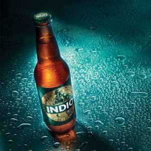 Bottle of Indio on wet surface with beads of water