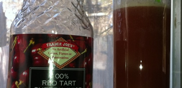 An empty bottle of Trader Joe's 100 percent Red Tart Cherry Juice next to a Collins glass full with a Cherry lime Rickey