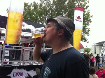 Fervere drinks from his glass Toronto's Festival of Beer mug, in front of the Molson Canadian exhibition.