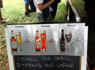 A pre-printed list displaying the three type of Krombacher beer, taped onto a sandwich board showing options for 1 token for a small serving and 2 tokens for a large.