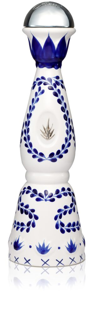 A white ceramic bottle of Clase Azul Reposado with blue-leaf motif and and embossed silver agave leaf