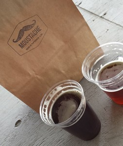 Two plastic pints of Moustache Brewing beer, one amber and one dark, by a paper bag with Moustache's logo