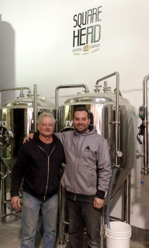 Dave and Brad Jordan of Square Head Brewing standing in front of their brewery equipment