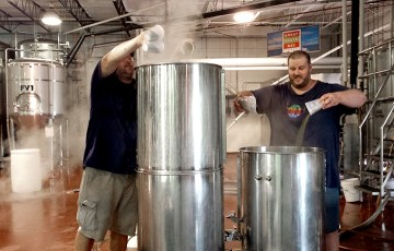 Chris and Gregg Kelley add 3 cups of hops at once to a boiling wort