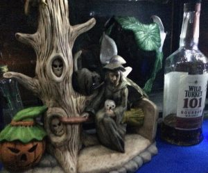 A ceramic Halloween decoration next to a bottle of Wild Turkey 101 Bourbon