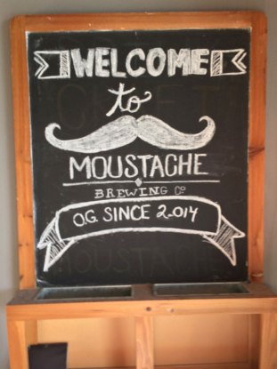 Chalk board at entrance of Moustache Brewing Co in Riverhead, NY, with writing welcoming customers