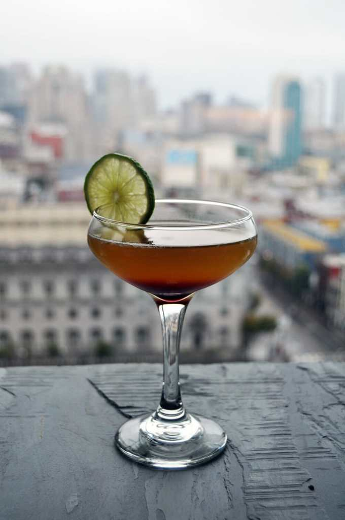 Cocktail with lime garnish and beautiful view