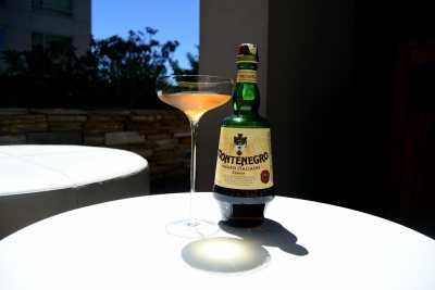 Cocktail with a long stem in front of bottle of liqueur