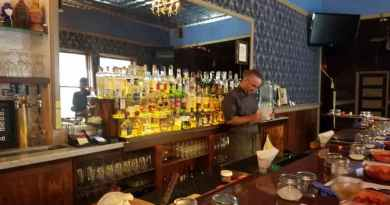 Many jars in front of bar with many bottles behind it
