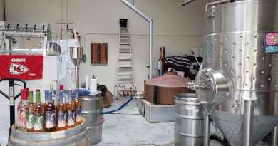 Several stills and bottles in front of bar