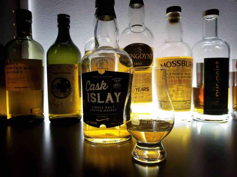 Whisky glass next to many whisky bottles