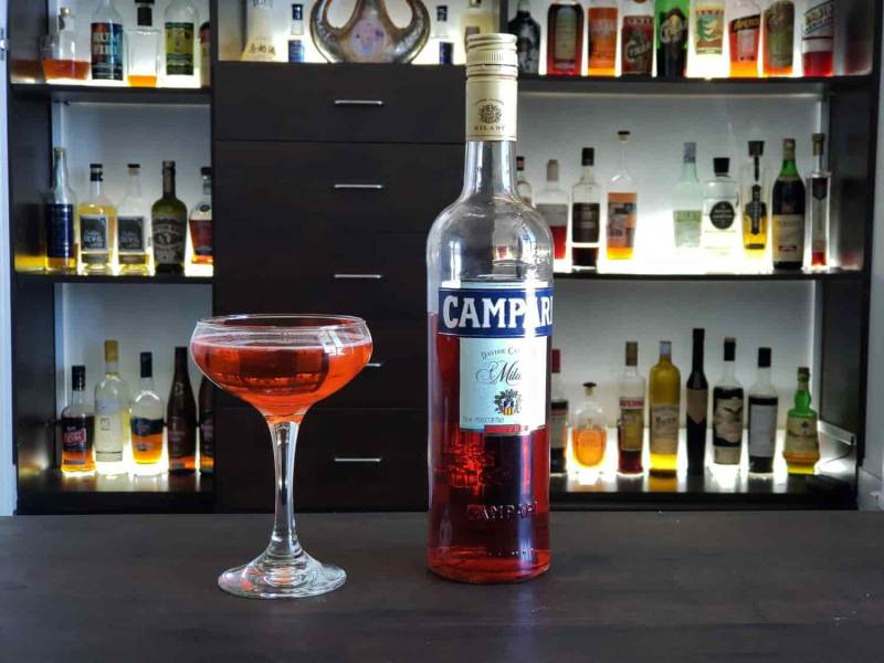 Cocktail next to bottle of Campari