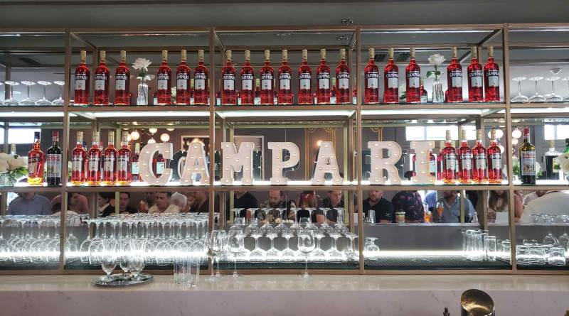 Many bottles of Campari with sign