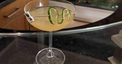Yellowish cocktail in glass with silver pick with lime garnish ontop of glass surface