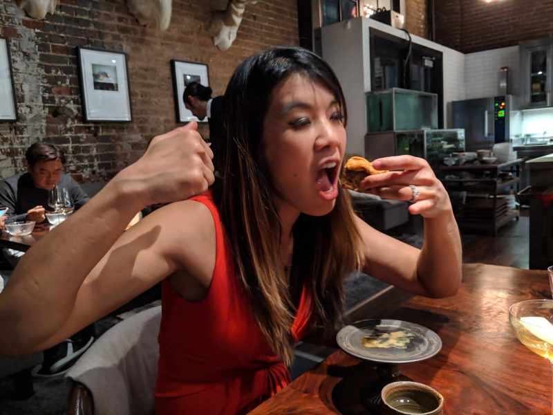 Woman in red top eating a chicken wing