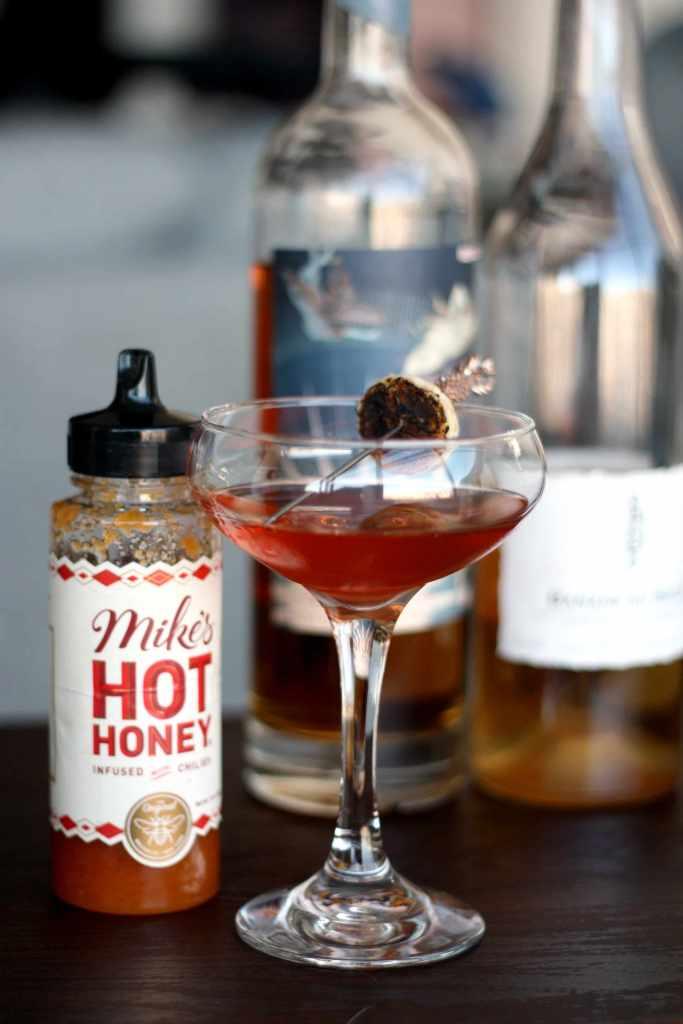cocktail in front of honey bottle and banana liqueur bottle