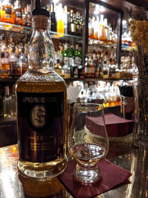 Springbank 18 bottle next to tasting glass with bottles of whisky behind