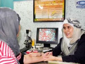 Doctor Puti Rita Liswari (kanan) memeriksa pesakinya menggunakan ujian analisa darah tetapi memberikan ubatan herba di kliniknya di Bandung.